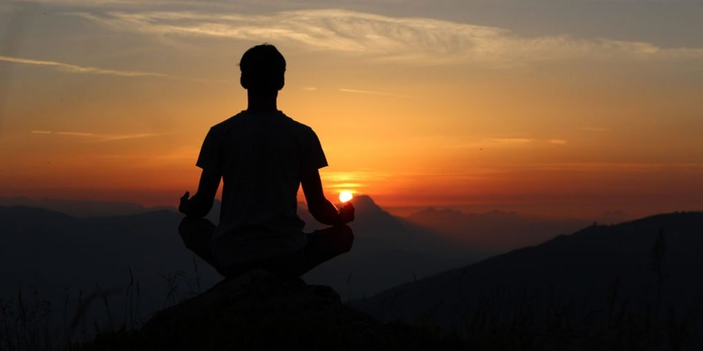 Man doing yoga during sunset for personal development