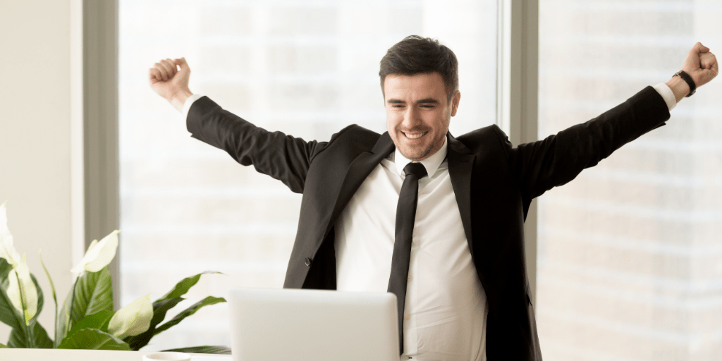 happy-motivated-businessman-in-suit-raising-hands-looking-at-laptop